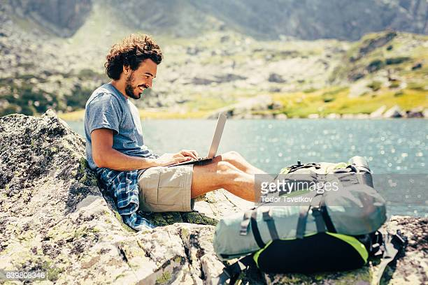 Man using a laptop in the mountain
