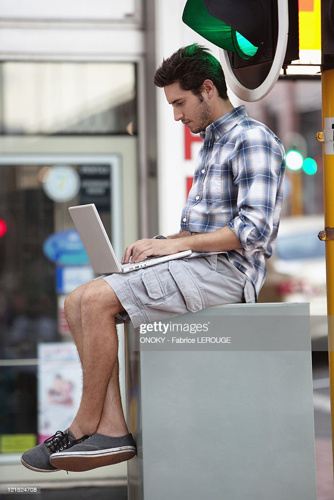 Man using a laptop near traffic light : Stock Photo