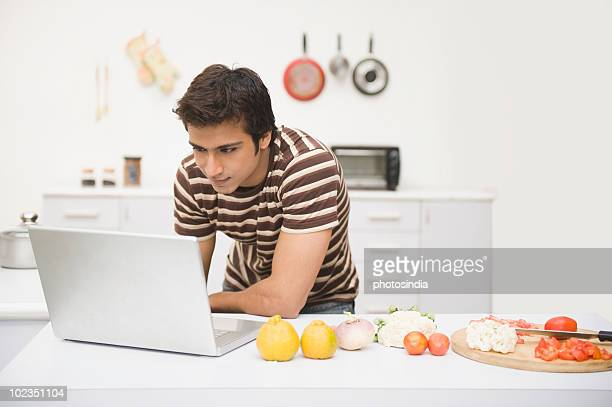Man using a laptop on a kitchen counter with vegetables