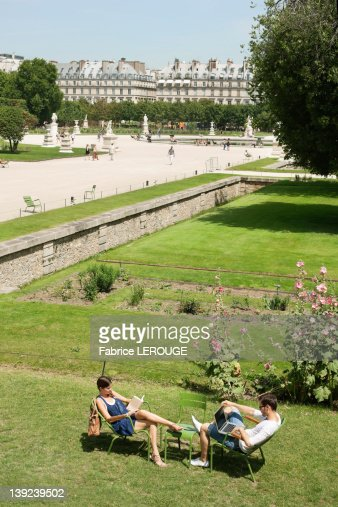 Man using a laptop with a woman reading a magazine in garden, Jardin des Tuileries, Paris, Ile-de-France, France