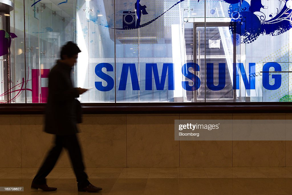 A man using a mobile phone as he walks past a Samsung Electronics Co. advertisement displayed at the company's Seocho office building in Seoul, South Korea, on Friday, March 15, 2013. Samsung Electronics's President of visual display Yoon Boo Keun and President of mobile communications J.K. Shin were appointed as co-chief executive officers following the company's shareholder meeting today, joining Vice Chairman Kwon Oh Hyun, who will also retain his position as co-CEO. Photographer: SeongJoon Cho/Bloomberg via Getty Images