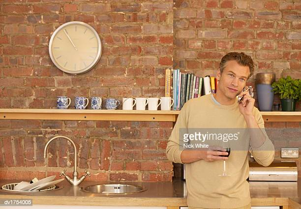 Man Using a Mobile Phone in a Kitchen with a Brick Wall