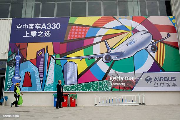 A man using a mobile phone stands near an advertisement for the Airbus A330 aircraft manufactured by Airbus Group NV during the China International...
