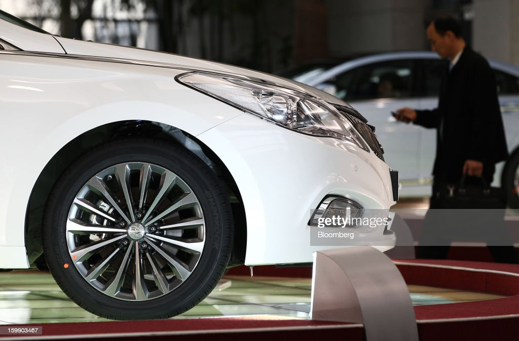 A man using a mobile phone walks past a Hyundai Motor Co. 5G Grandeur sedan on display in the showroom at the company's headquarters in Seoul, South Korea, on Tuesday, Jan. 22, 2013. Hyundai Motor Co. is scheduled to release fourth-quarter earnings on Jan. 24. Photographer: SeongJoon Cho/Bloomberg via Getty Images