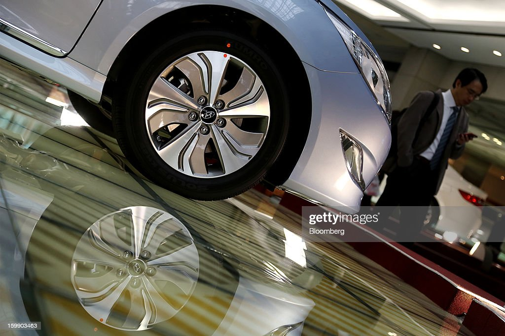A man using a mobile phone walks past a Hyundai Motor Co. Sonata hybrid vehicle on display in the showroom at the company's headquarters in Seoul, South Korea, on Tuesday, Jan. 22, 2013. Hyundai Motor Co. is scheduled to release fourth-quarter earnings on Jan. 24. Photographer: SeongJoon Cho/Bloomberg via Getty Images
