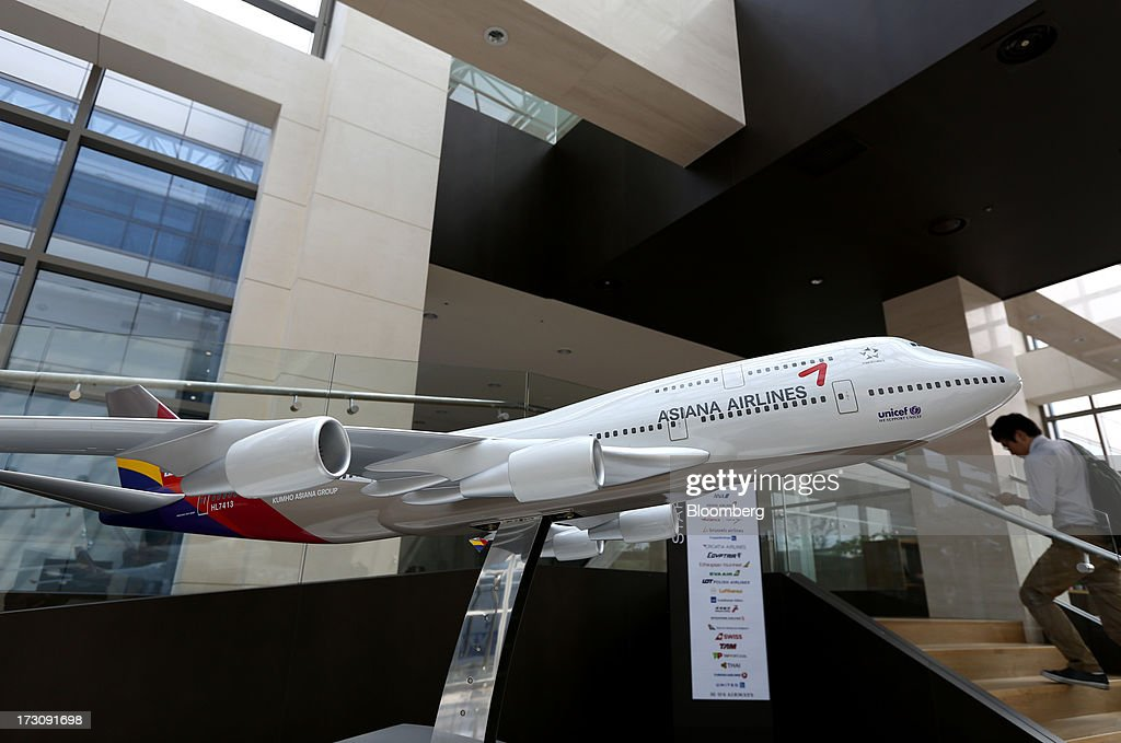 A man using a mobile phone walks past an Asiana Airlines Inc. model aircraft displayed at the company's headquarters in Seoul, South Korea, on Sunday, July 7, 2013. A Boeing Co. 777 flown by South Korea's Asiana Airlines crashed while landing in San Francisco yesterday, killing two people as passengers escaped down emergency slides before a fire swept through the plane. Photographer: SeongJoon Cho/Bloomberg via Getty Images