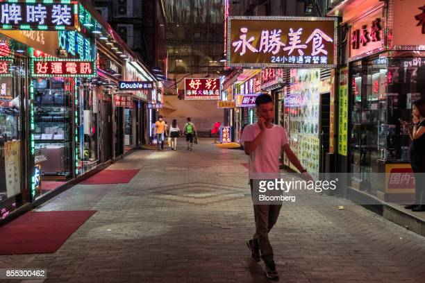 A man using a mobile phone walks past stores at night in Macau China on Wednesday Sep 27 2017 Junkets flush with high rollers full hotels charging...