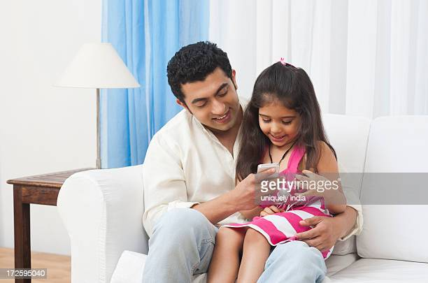 Man using a mobile phone with his daughter