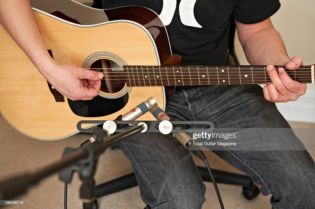 A man using a pair of sE Electronics sE1a condenser microphones to record his acoustic guitar, photographed during a studio shoot for Total Guitar Magazine, April 13, 2012.
