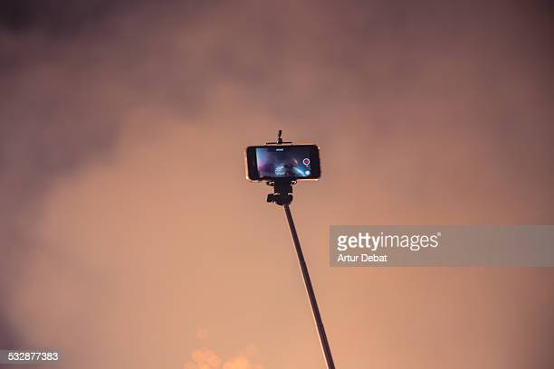 Man using a selfie stick to recording the Correfocs firework show from high angle view at night with his smartphone