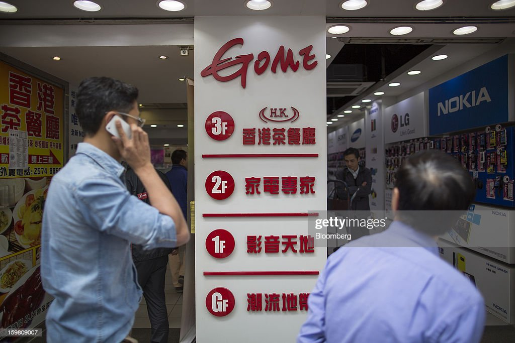 A man using a smart phone walks past the entrance of a Gome-branded store in the shopping district of Causeway Bay in Hong Kong, China, on Monday, Jan. 21, 2012. Gome Electrical Appliances Holding Ltd.'s stocks tumbled in Hong Kong after the company confirmed a report it is closing Gome-branded stores in the city. Photographer: Jerome Favre/Bloomberg via Getty Images