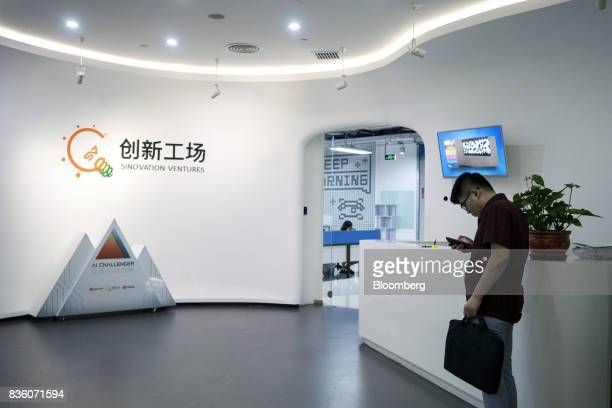 A man using a smartphone stands at the reception area of the Sinovation Ventures headquarters in Beijing China on Tuesday Aug 15 2017...