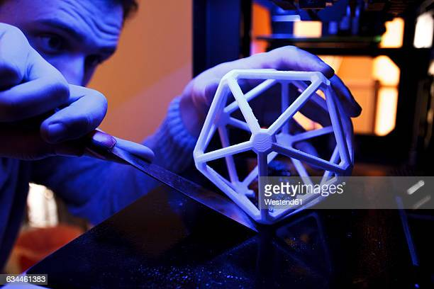 Man using a spatula to separate a 3D geometric figure from the platform of a 3D printer