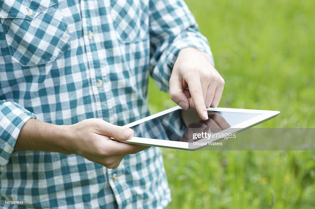 Man using a tablet in a summer park : Stock Photo