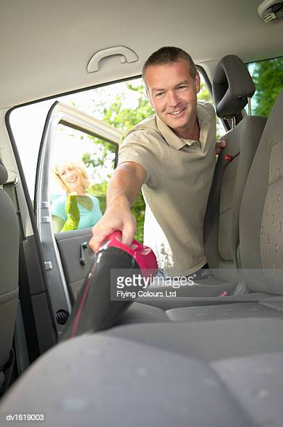 Man Using a Vacuum Cleaner to Clean Car Seats, While a Woman Cleans a Car Door Window