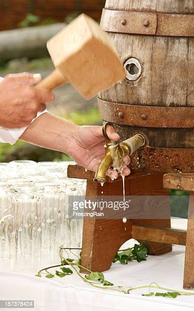 Man using a wooden mallet on a beer barrel