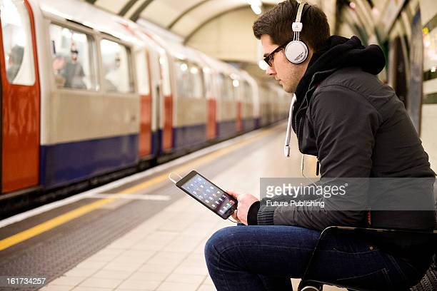 A man using an Apple iPad Mini tablet computer whilst waiting for an underground train on January 14 2013