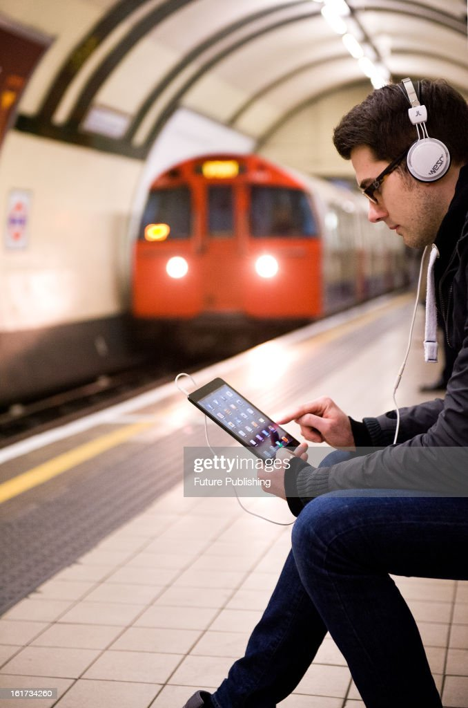A man using an Apple iPad Mini tablet computer whilst waiting for an underground train on January 14, 2013.
