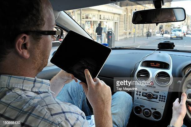 A man using an Apple iPad tablet computer whilst sitting in a car session for Tap Magazine taken on September 29 2011