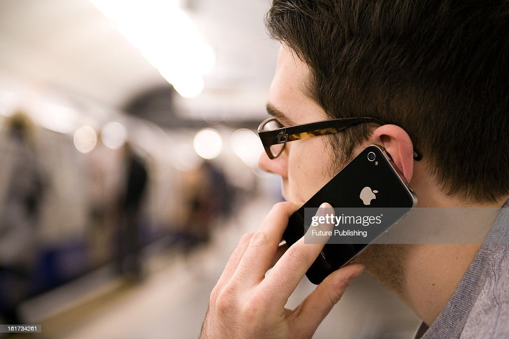 A man using an Apple iPhone 4S smartphone whilst waiting for a train on January 14, 2013.