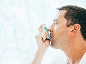 A man is using an asthma inhaler at home .