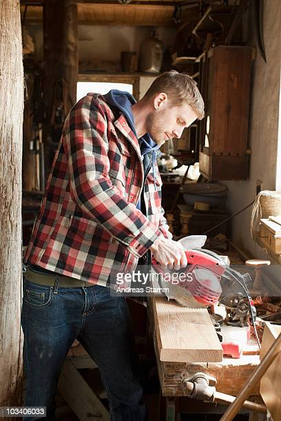 A man using an circular saw on a plank in a workshop