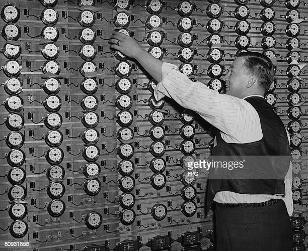 A man using an electrical system to set a large number of clocks simultaneously at the New Haven Clock Co factory New Haven Connecticut circa 1935