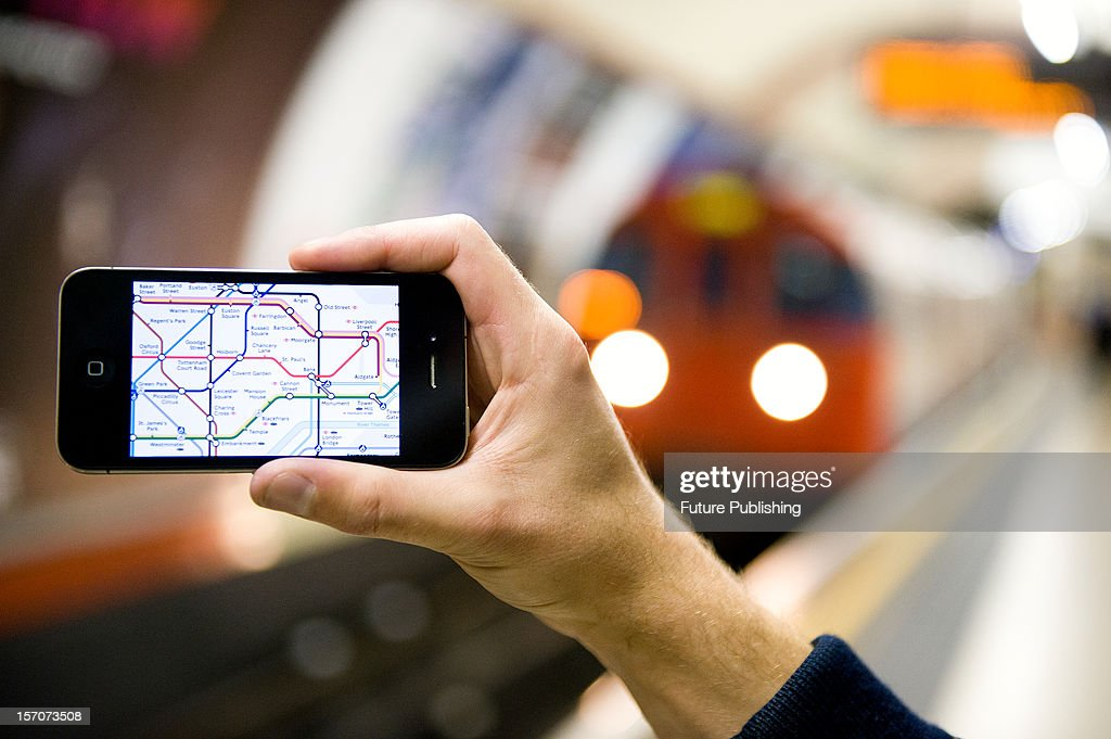 A man using an iPhone to view a map of the London Underground whilst waiting for a tube train, October 4, 2012.