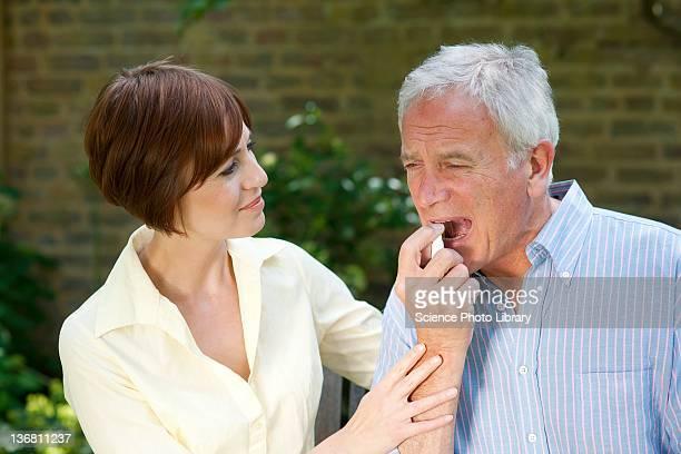 Man using angina spray