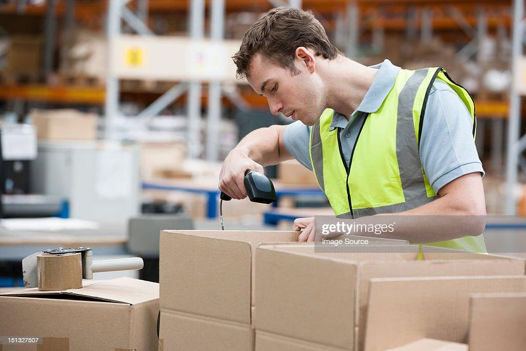 Man using barcode reader in warehouse : Stock Photo
