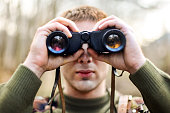 Young man looking through binoculars (army or hunting concept)
