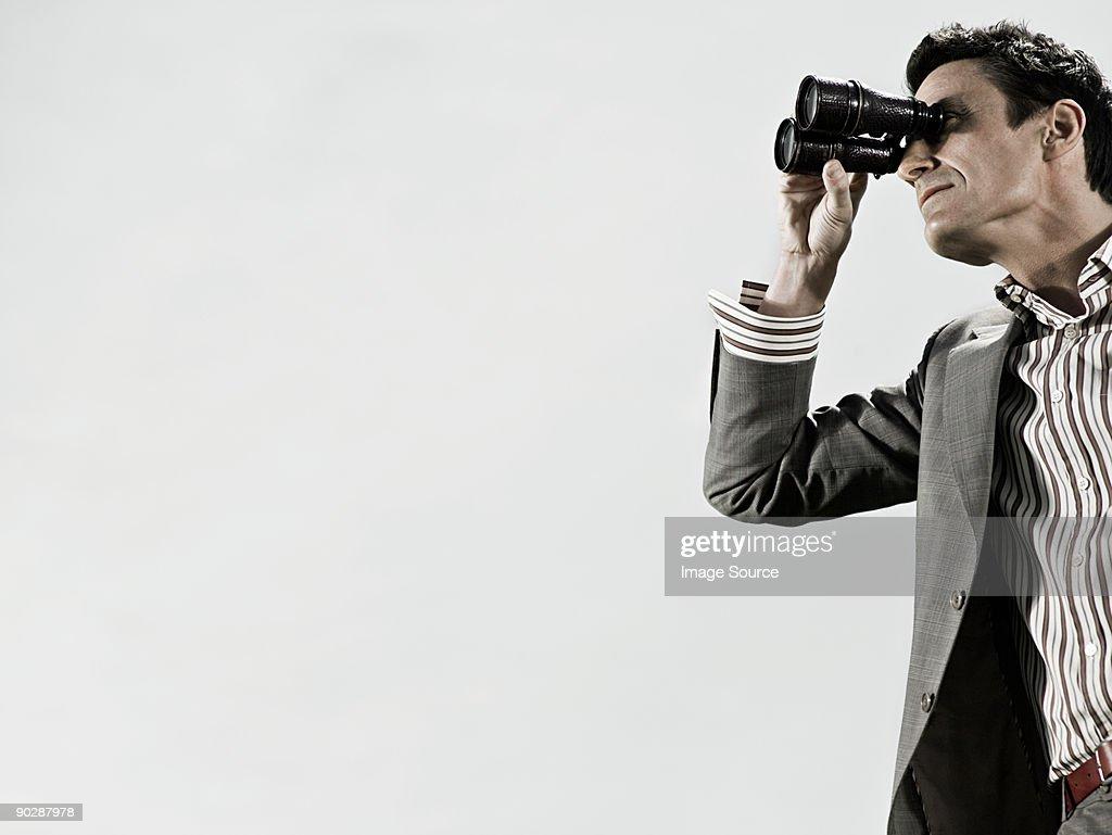 Man using binoculars : Stock Photo