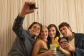 Man using camera phone with friends holding cocktails