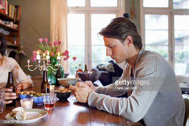 Man using cell phone at dinner table