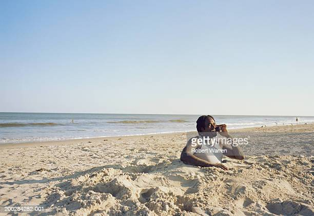 Man using cell phone, buried in sand, side view