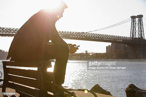 Man using cell phone by urban bridge