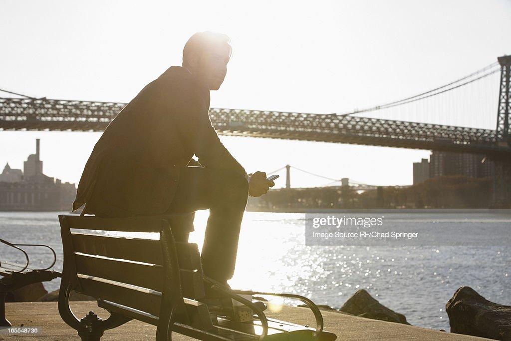 Man using cell phone by urban bridge : Stock Photo