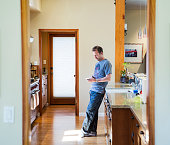 Man using cell phone in kitchen