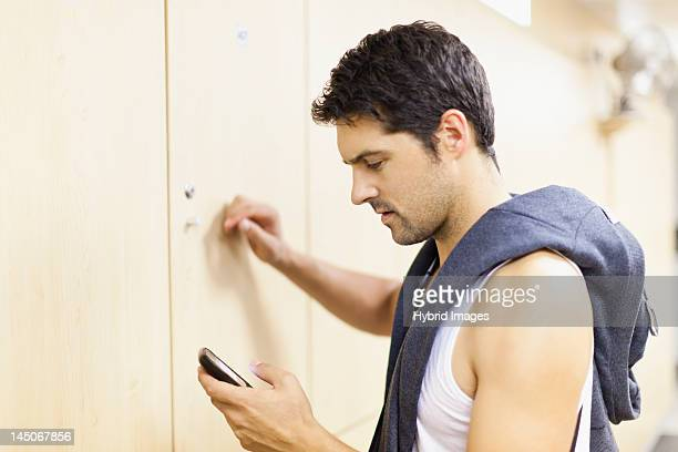 Man using cell phone in locker room