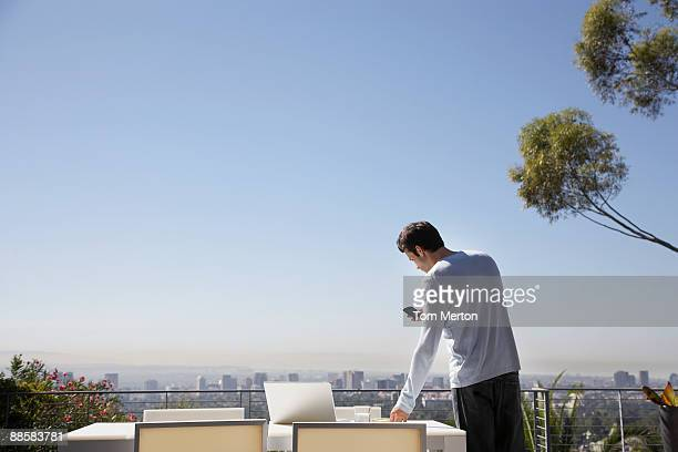 Man using cell phone on balcony