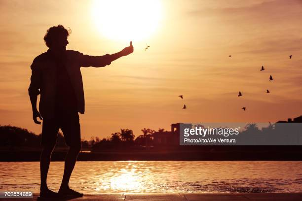 Man using cell phone to photograph sunset
