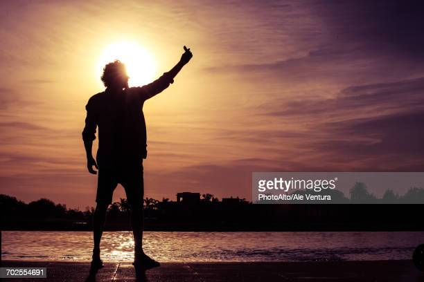 Man using cell phone to take a selfie at sunset