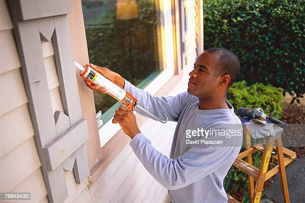 Man Using Chemical on Window