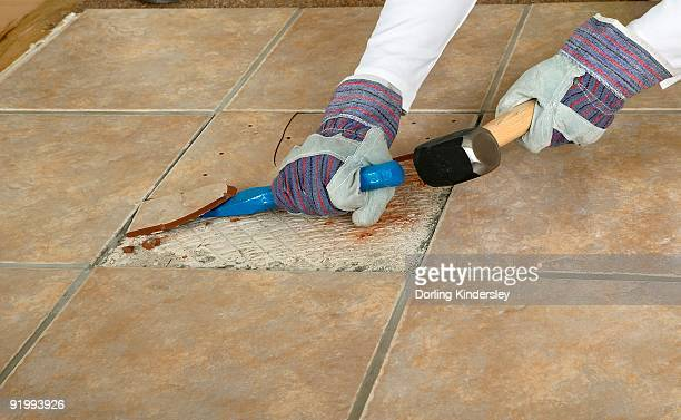 Man using club hammer and chisel to remove marble tile from floor, close-up