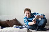 Man using computer game controls sitting on sofa