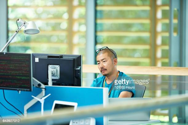Man using computer in modern office.