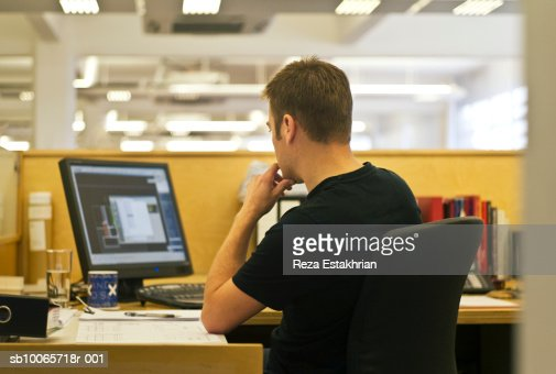 Man using computer in office, rear view : Stock Photo