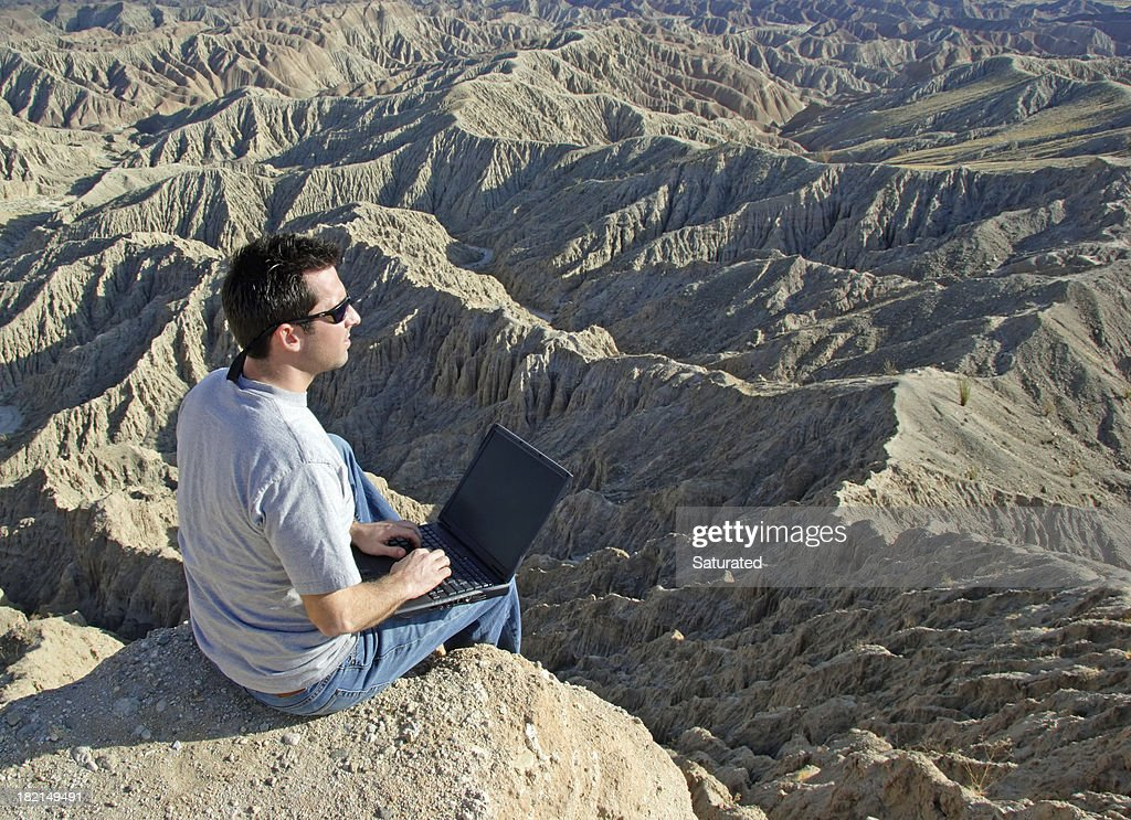 Man Using Computer in the Wilderness : Stock Photo