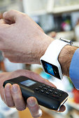 Man Using Contactless Payment App On Smart Watch In Store
