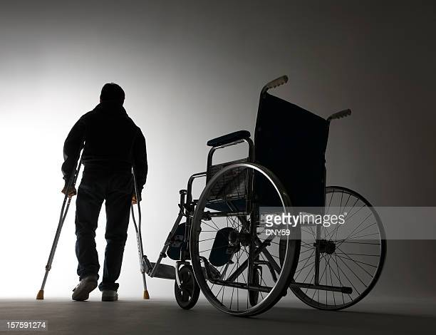 Man using crutches walking away from wheelchair